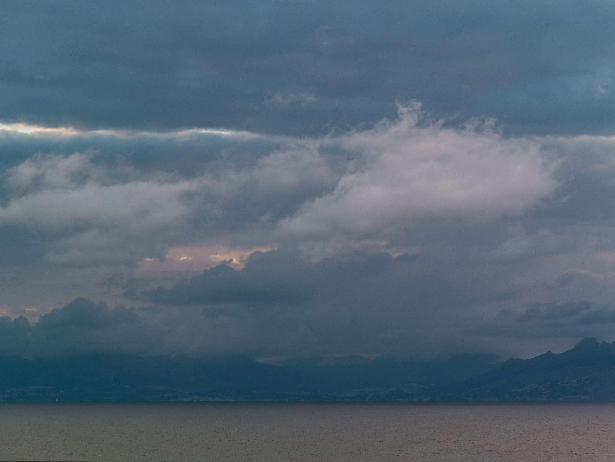 Clouds over the mountains on the coast of Spain from the sea.