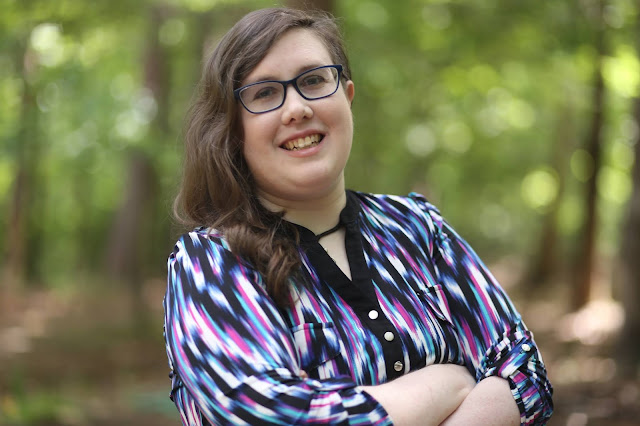 Photo of the author, a white woman with brunette hair, wearing bold blue glasses and a multicolor shirt, standing in a forest.