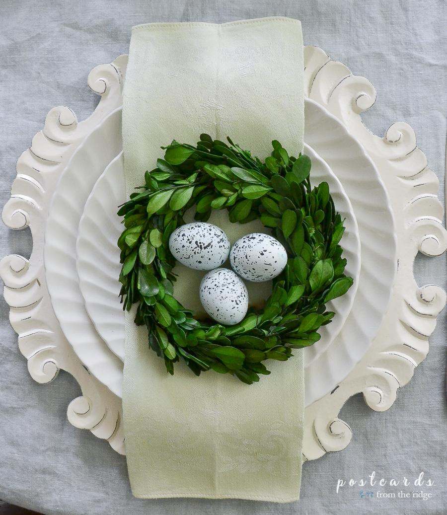 boxwood wreath with ceramic robin eggs on vintage ironstone dishes
