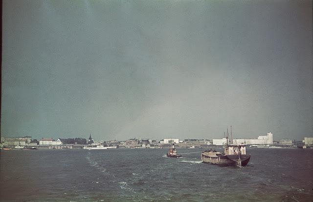 Värillinen valokuva. Kuvassa vesistömaisema, taustalla siintää kaupunki.Etualalla on vene.