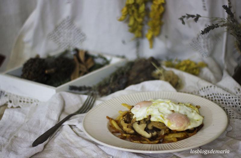 Huevos fritos sobre champiñones salteados y patatas pajas fritas