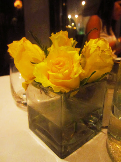 yellow roses in a square vase on a dining room table
