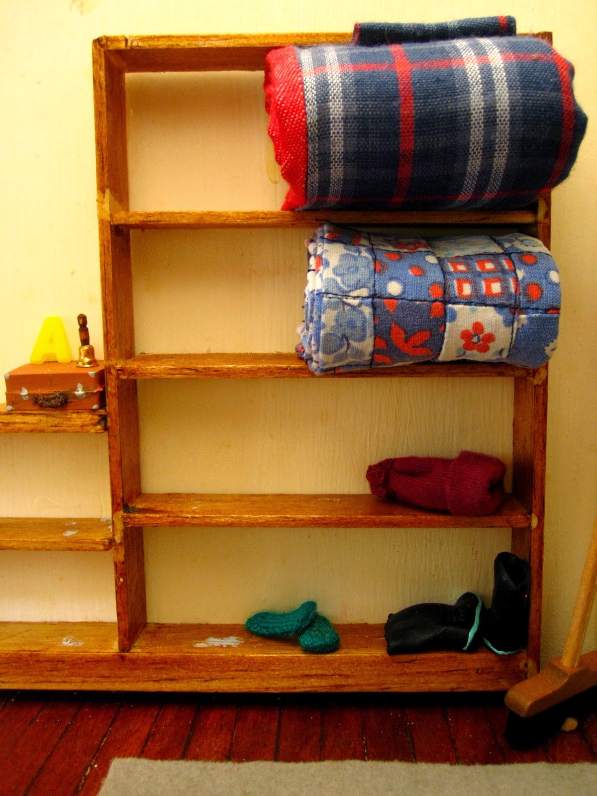Miniature shelving with a rolled up doona on the top shelf and a folded vintage quilt on the shelf below, On the bottom shelf is a pair of green socks and a pair of gumboots.