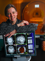 Cheryl Olman leaning on a computer screen showing brain scans