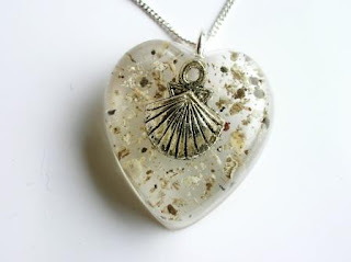 Heart shaped pendant with ashes and a charm