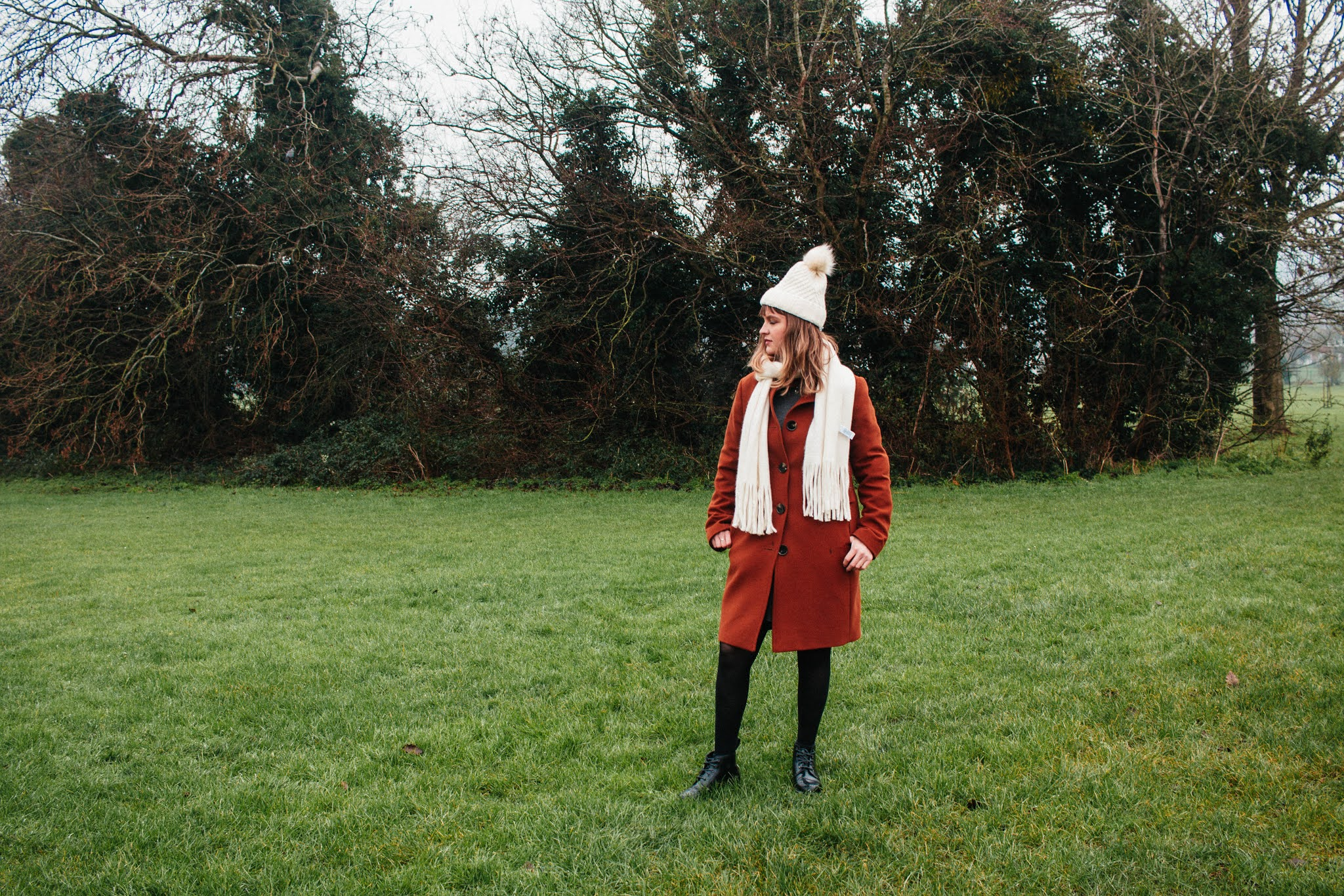 Girl dressed in coat, hat & scarf, in nature. January 2021 habits and goals blog post