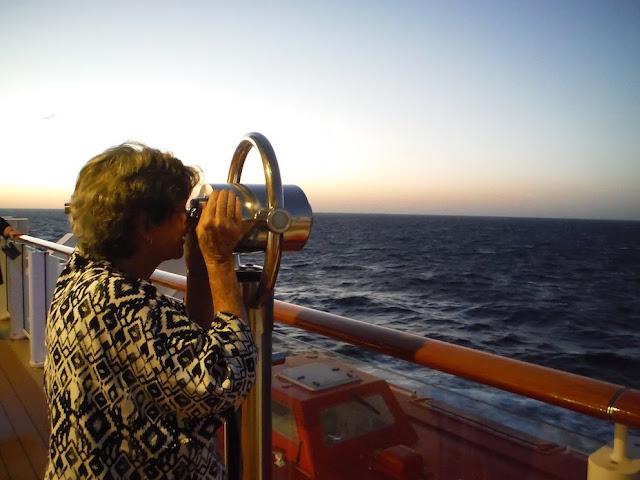Woman looks through binoculars across the sea
