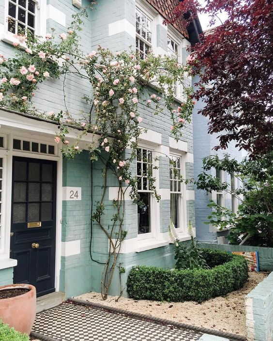 Light blue painted brick, climbing roses, black door  beautiful home exterior seen on Hello Lovely Studio