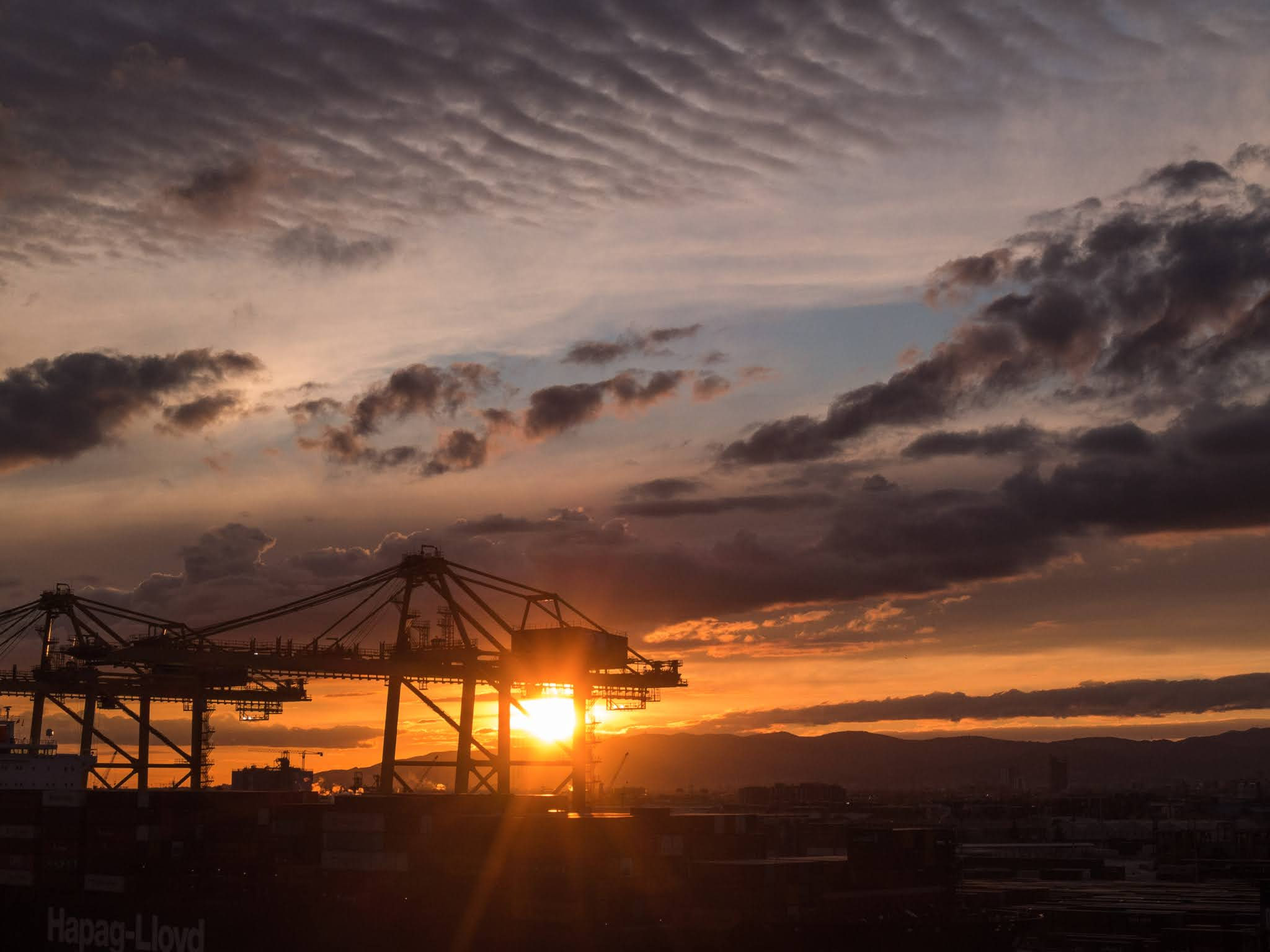 Sun shining through a gantry crane in the port of Barcelona during sunset.