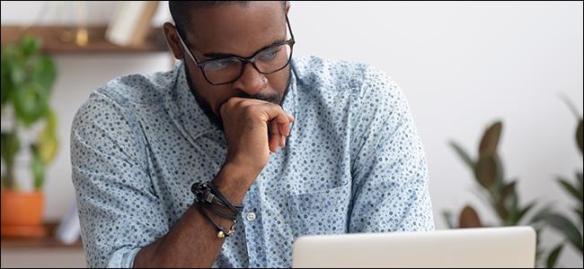 رجل يحدق في حاسوبه المحمول.