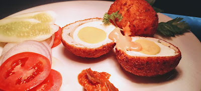 Garnished scotch eggs with green salad, pickle,sauce and parsley for scotch eggs recipe