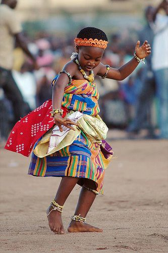 A young Ghanaian child doing Akan Adowa dance majestically in her traditional beautiful and colorful kente apparel