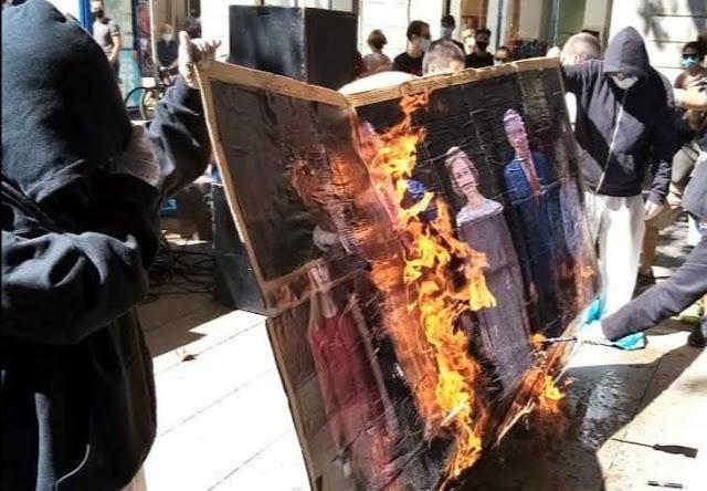 Varios jóvenes queman una imagen de la familia real durante la manifestación convocada por Arran