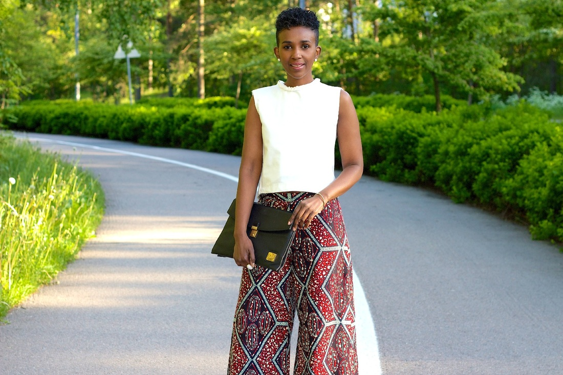 street photo of woman wearing a white top, afrrican print palazzo pants with a blag clutch bag in hand