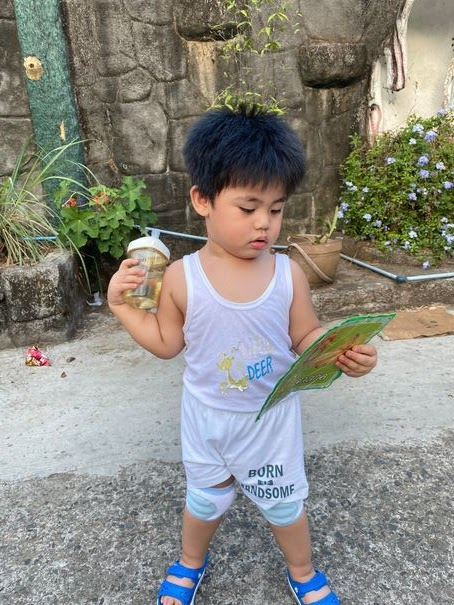 Toddler holding a milk bottle and flash card during his unlimited playtime called Unli Dapa