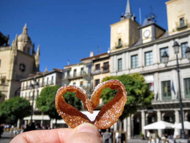 Heart shaped piece of a florone against the backdrop of Plaza Mayor in Segovia, Spain