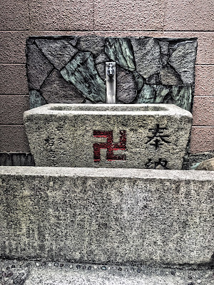 Swastika on chozubachi, water-filled basin, at Shinto Shrine near Nishikujo station, Osaka, Japan. Photo by Sydney Solis