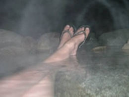 Exterior night photo with feet soaking in natural hot springs.