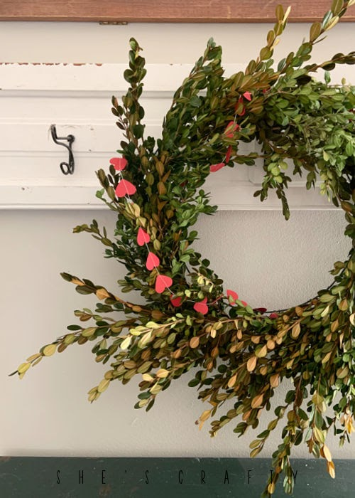 Paper Heart banner placed around boxwood wreath