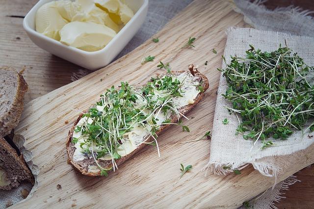 Tabla de madera con una rebanada de pan integral untado con queso crema y top de berros