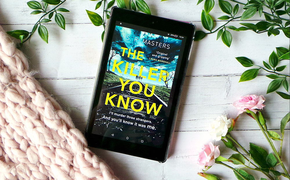 Kindle fire screen showing the cover for The Kille you know next to a chunky knit pink blanket and some roses. The cover has 4 people in the distance walking on a railway track and the title written in yellow