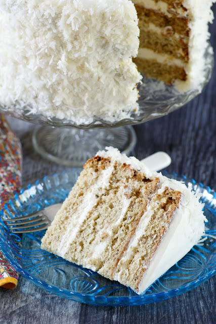 banana cake with 4 layers of cake, fluffy white meringue frosting and bright white coconut