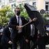 Μητσοτάκης: Με διαφημιστική ομπρέλα ξενοδοχείου στην κηδεία Θεοδωράκη