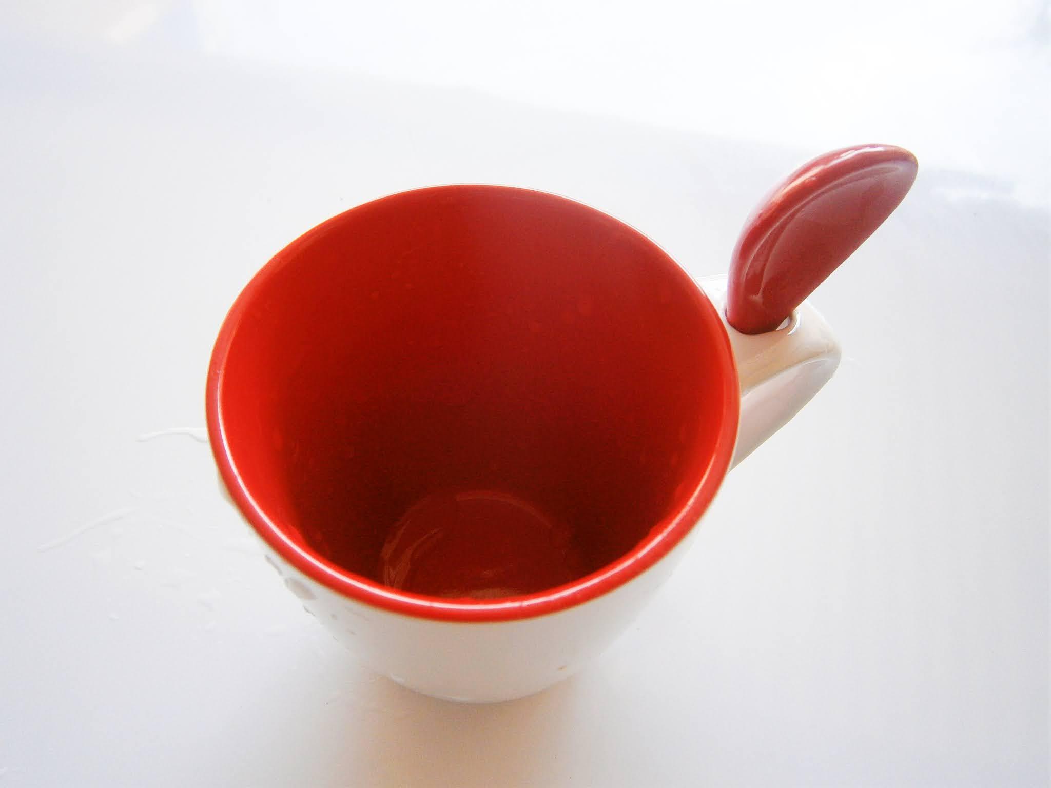 fotografía de taza de color rojo puesto sobre fondo blanco