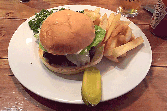 Posh cheese burger, chips and gherkin.