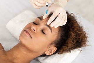 Woman receiving Botox injection in her forehead