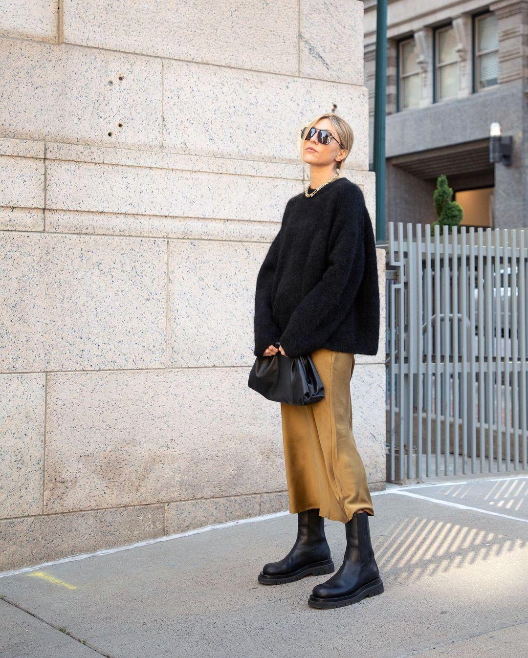 Fall Outfit Idea Stepsofstyle in Oversized Black Sweater, Bottega Veneta Clutch Bag, Camel Silk Midi Skirt, and Black Lug Sole Boots