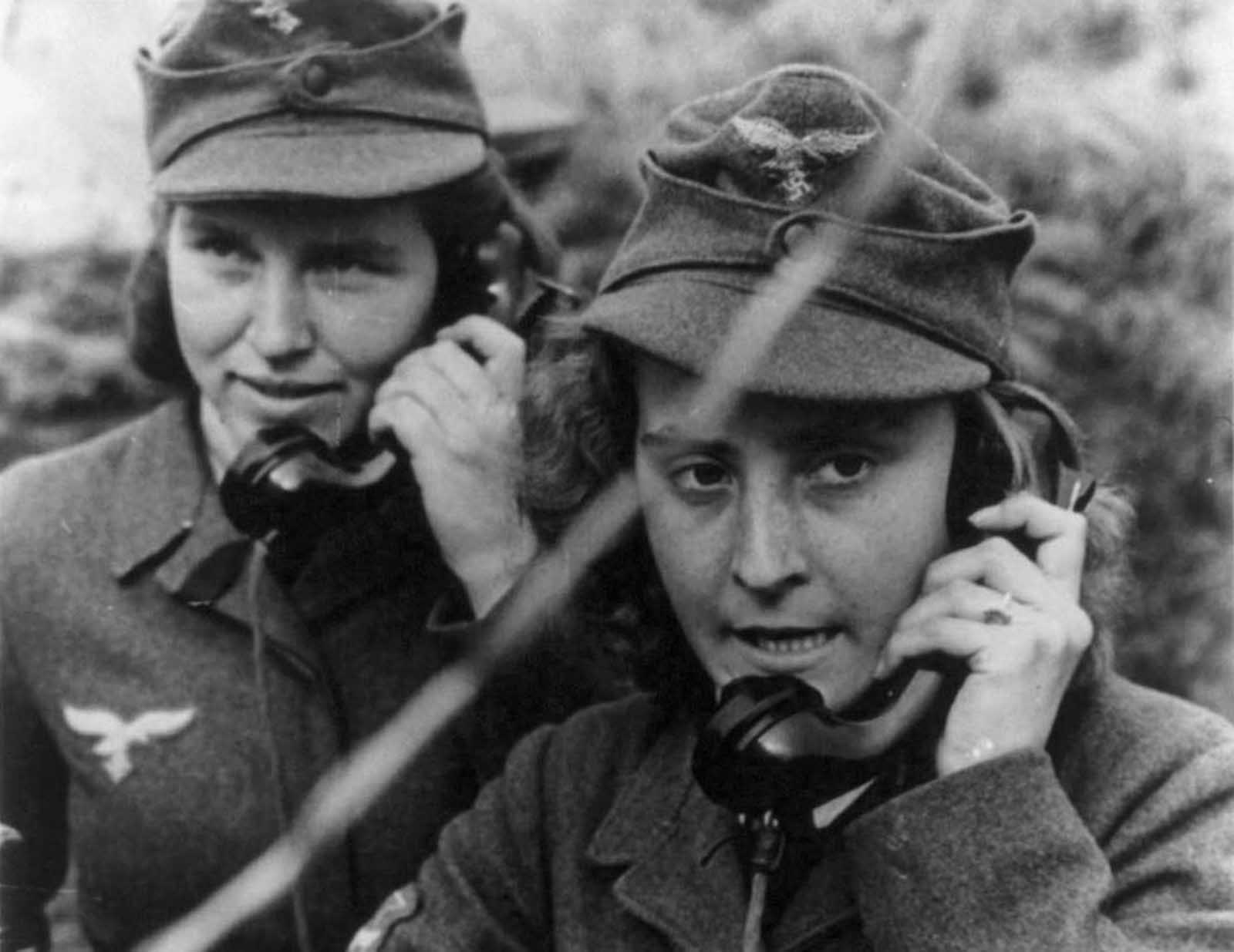 Two women of the German anti-aircraft gun auxiliary operating field telephones during World War II.