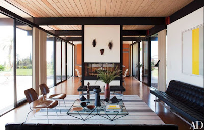 Interior design mid-century style with black leather sofa wooden chairs