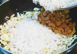 Adding boiled rice over scrambled eggs and Chicken pieces for making chicken fried rice recipe