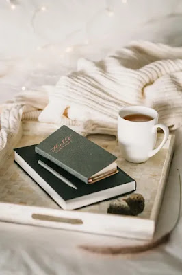 Journals in a tray with coffee