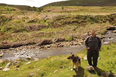 Rich and our dog standing by a shallow stream.