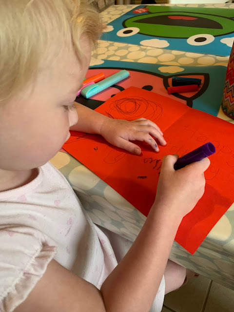 A toddler writing a birthday card for a cat