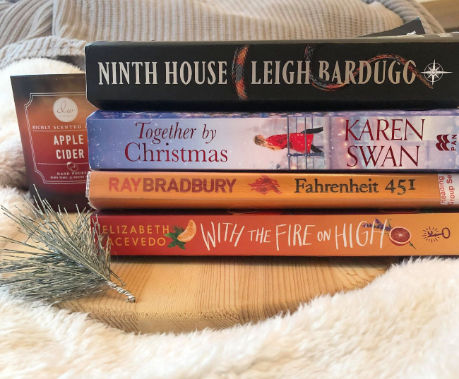 Stack of four books next to an Autumn candle