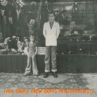 black and white photo of Ian Dury and a young boy standing outside a department store window