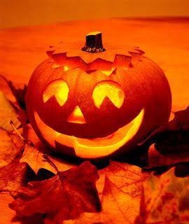 Calabaza de halloween cortada y encendida sobre unas hojas de otoño