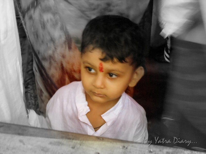 A small kid in a melancholic mood during the festival of Ganesh Visarjan, Mumbai