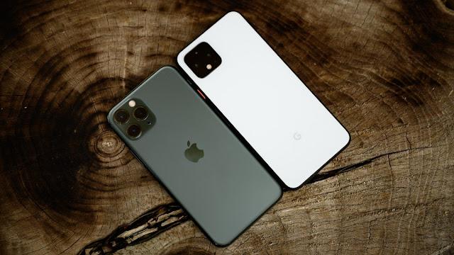 Apple iPhone بجوار Google Pixel على مقعد خشبي.