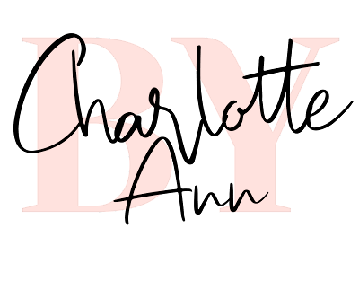 By Charlotte Ann logo: handwritten black 'Charlotte Ann' over a large, pale pink formal text reading 'BY'