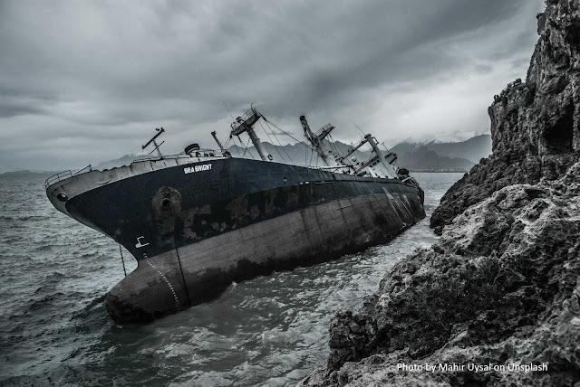 Navio adernado ao lado de paredão de rochas