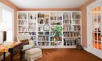 Bir ev odasındaki duvardan duvara yapılmış kişisel kütüphane ve raflarındaki kitaplar