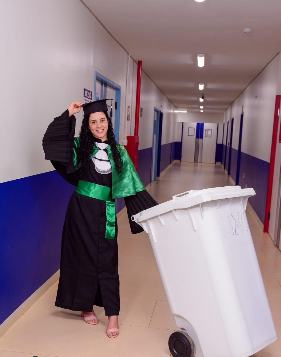 Zeladora posa para fotos de formatura com materiais de limpeza