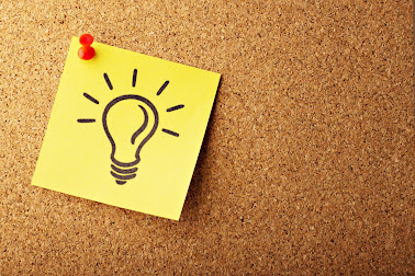 Yellow post-it on a corkboard with idea light bulb cartoon drawn on it