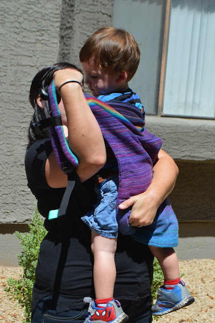 Woman is seen holding baby's bottom with one hand as she slides the other arm into the shoulder straps