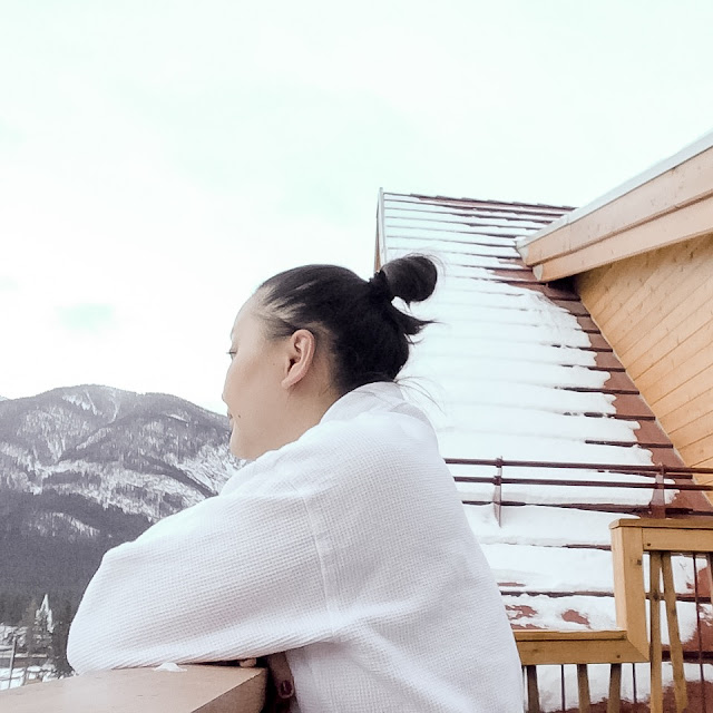 girl  in robe looking at view of banff