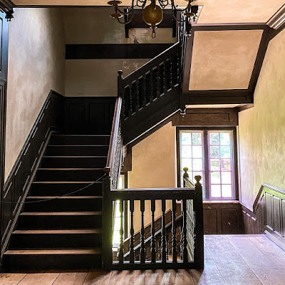 Interior staircase at Pennsbury Manor seen fr second floor landing. Light tan plaster walls are accented with wood trim and panelling. There is a casement window on the lower landing and a brass chandelier overhead.